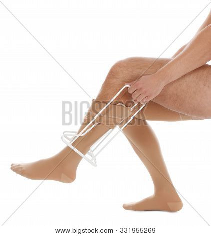Man Putting On Compression Garment With Stocking Donner Against White Background, Closeup