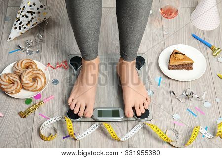 Woman Using Scale Surrounded By Food And Alcohol After Party On Floor. Overweight Problem
