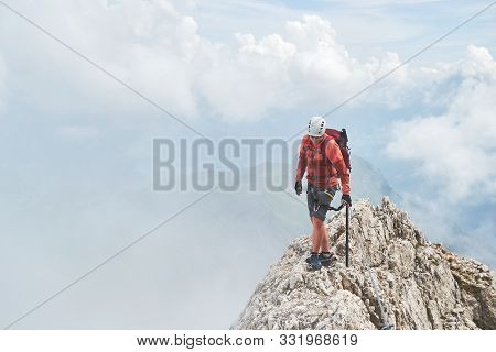 Man On A Narrow Mountain Ridge Surrounded By Fog, Up On Via Ferrata Eterna (cadore Brigade) At Marmo