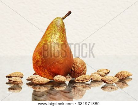 Still Life With Sweet Ripe Pear, Walnut And Salted Almonds In Their Nutshells Against High Key Backg
