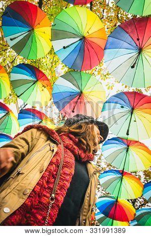Gay Woman With Rainbow Colored Umbrellas. Woman Walking Under Rainbow Umbrellas In Gay Parade. Gay P