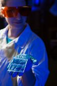 Female researcher in protective glasses holding in hand an agarose gel plate with results of DNA analysis poster