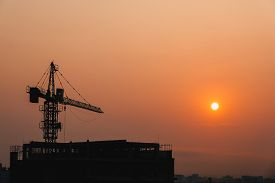 Crane building construction site at sunset or sunrise. Stock photo image silhouette of construction