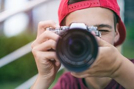Teenage boy taking photos outdoors. Young man works reporter, outdoors. Caucasian guy holds a photo camera and capturing photos. 15 years old teenager is with digital photo camera