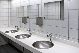Blurred White Washbasins And Shiny Faucets In Toilet With Flare Light. Use As Background, Backdrop,
