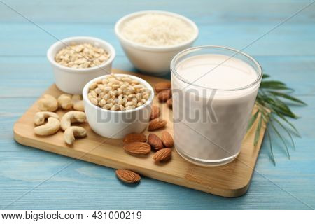 Vegan Milk And Ingredients On Light Blue Wooden Table, Closeup