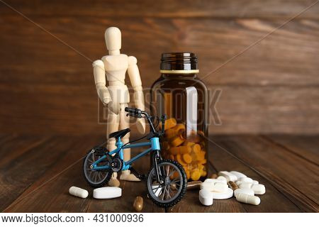 Pills, Sportsman And Bike Model On Wooden Background. Using Doping In Cycling Sport Concept