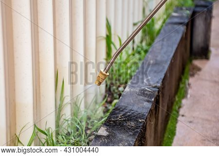 Spraying Weed Killer Herbicide To Control Unwanted Plants And Grass Near A Backyard Fence