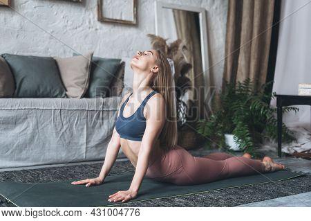 Urdhva Mukha Svanasana. Young Sporty European Woman Doing Upward Facing Dog Pose While Exercising In