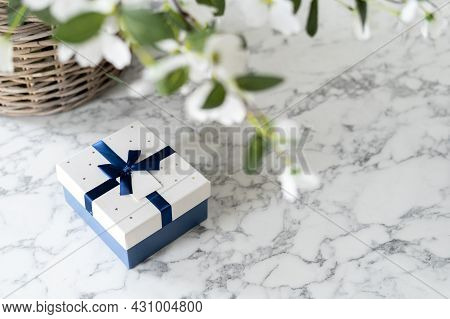 Gift Box With Ribbon And Bow Under Luscious Flowers, White And Blue Colours, Big Woven Basket With G