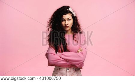 Irritated Woman With Crossed Arms Looking At Camera Isolated On Pink