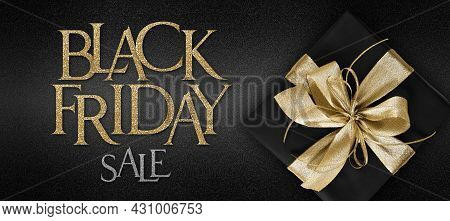 Gift Card, Black Friday Sale Text And Black Package Wrapped With Golden Ribbon Bow Isolated On Black