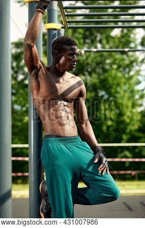 Muscular Young Man Exercising At The Sports Field. African Man Looking To The Side While Doing Horiz
