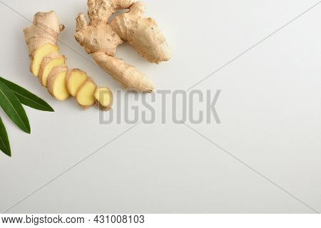 Fresh Ginger Root With Sliced Portions On White Table And Leaves. Top View.
