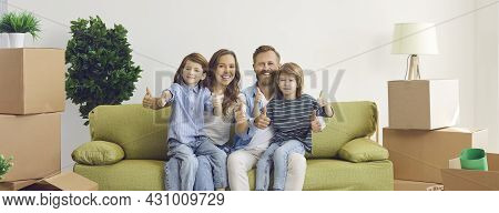 Happy Mother, Father And Children Sitting On Sofa In New Home And Showing Thumbs Up
