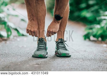 Smart watch exercise walking sport man preparing to go walk run at park outside wearing smarwatch tech lacing running shoes in autumn fall nature.