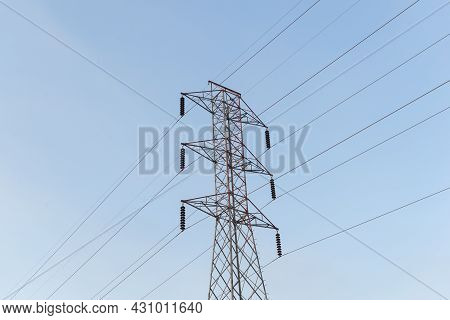High-voltage Power Lines Electricity Transmission Pylon On Blue Sky Background. Part Of High-voltage