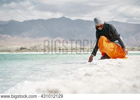 Asian Woman Female Tourist Touching The Water Of A Salt Lake