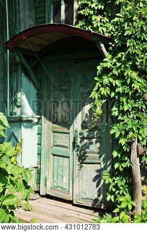 Old Green Wooden Door. A Door With Peeling Paint. The Entrance To The House Is Through A Door And A