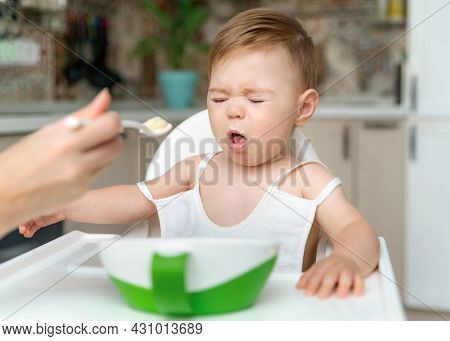 Charming Little Baby Boy 8-11 Months Doesn't Want To Eat Porridge From Spoon With Mom At Home. Kid D