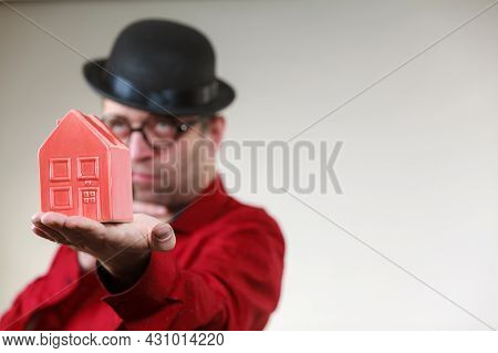 Adult Man Wearing Funny Hat And Eyeglasses Holding Small Red House Model. Guy Being Real Estate Agen