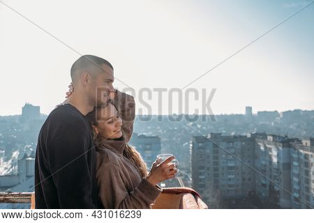 Young Couple Drinking Coffee On The Balcony Of The Apartment In The Morning. Young Happy Couple, New