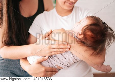 A Young Happy Female Couple And Their Child Are Enjoying Together At Home.same-sex Marriage And Adop