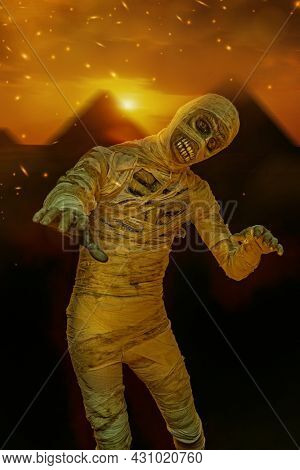 Ancient Egyptian mythology. Portrait of a scary evil mummy on a background of the Egyptian pyramids. Halloween.