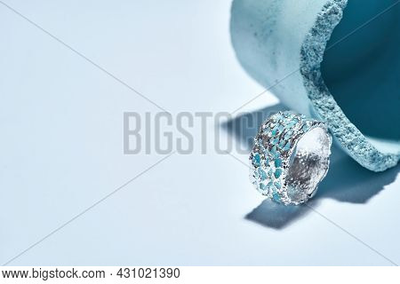 Macro Shot Of A Ring Made Of Silver Metal With Blue Enamel Arranged With Industrial Blue Concrete El