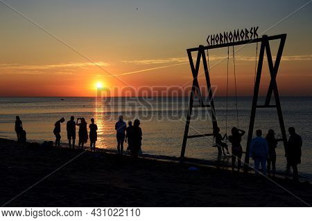 Chornomorsk, Ukraine - August 12: The People Are On The  Beach And Wooden Swing Enjoing Sunrise And