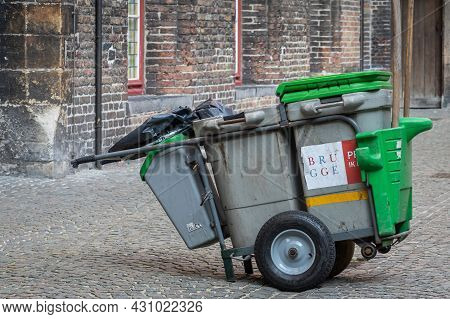 Brugge, Flanders, Belgium - August 4, 2021: Closeup Of Gray-green City-run Official Trashcans On Whe