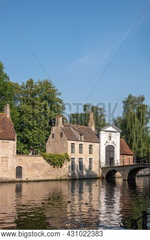 Brugge, Flanders, Belgium - August 4, 2021: Portrait, Sunlit Beguinage Entrance And Long Canal Facin