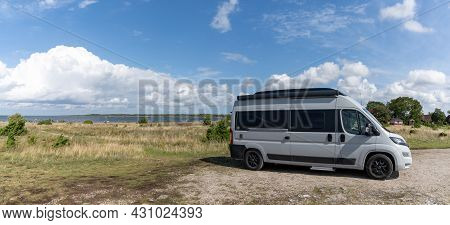 Ohessaare, Estonia - 15 August, 2021: Gray Camper Van Parked In A Gravel Lot Next To The Ocean Panor