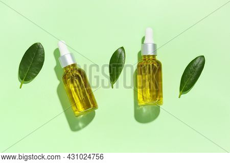 Two Glass Bottles With Natural Beauty Oil And Green Leaves With Shadows On Green Background Top View