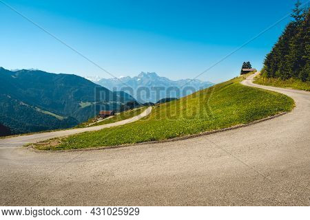 Alpine Panorama With Concrete Mountain Road U-turn And Green Pastures On A Summer Day With Clear Blu