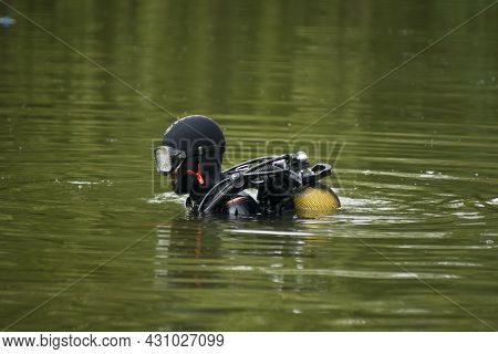 Diver Preparing To Dive. A Diver Prepares To Dive Into The Murky Water Of A Pond