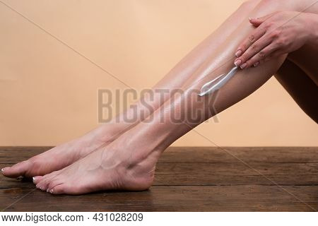 Young Woman Applying Body Lotion On Legs. Cosmetic Cream On Woman Leg With Clean Soft Skin. Applying