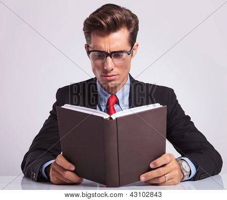 handsome young business man reading a book at his desk, on gray background