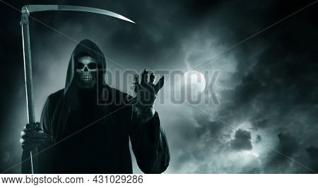 Grim reaper with scythe standing against  cloudy dramatic night sky with moon.The death  in a black hoodie.Halloween card with skeleton.Horror style  fantasy background with copy space.