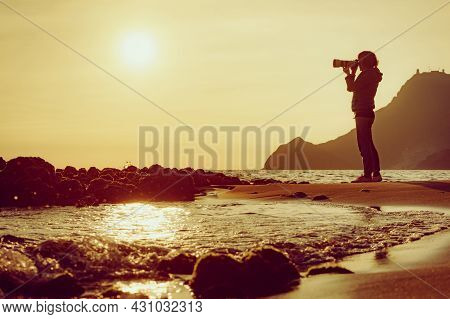 Tourist Woman With Camera Taking Travel Photo On Monsul Beach At Sunset. Cabo De Gata Nijar Natural