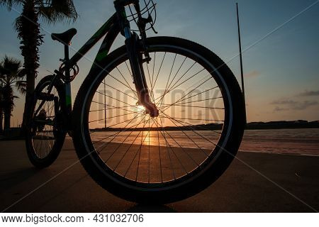 Silhouette Of A Bike At Sunset. The Sun Shines Through The Bicycle Wheel At The Sea Side Park