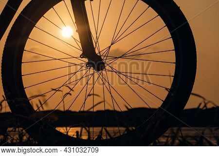 Close-up Silhouette Of A Bike Wheel At Sunset. The Sun Shines Through The Wheel Of A Bicycle, Select