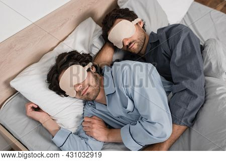 High Angle View Of Gay Couple In Eye Masks Hugging While Sleeping In Bed