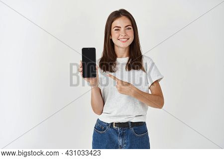 Young Brunette Woman Showing Blank Smartphone Screen And Pointing Finger At Mobile Phone, Smiling Sa