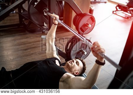 Handsome Bodybuilding Strong Man Working Out. Athletic Sporty Man Training Hard In The Gym.