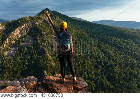 A Female Traveler With A Backpack Stands On The Edge Of The Mountain, A Rear View. A Young Woman Wit