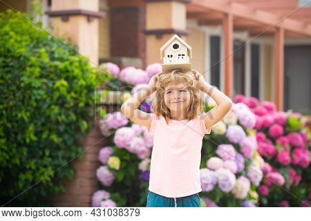 Real Estate, Housing And Family Concept. Funny Kid Holding Toy Wooden House Near New Home.
