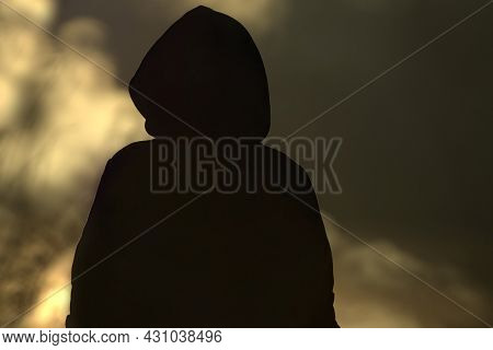 Concept: Arson. Hooded Figure Infront Of Fire Flames
