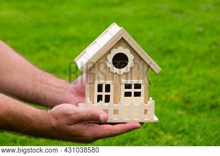 Male Hand Holding Model Of House Close Up. Small Miniature Toy House. Mortgage Property Insurance Dr