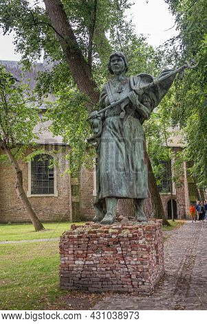 Brugge, Flanders, Belgium - August 4, 2021: Beguinage Courtyard. Closeup Of Ussr Bronze Statue Of Wo
